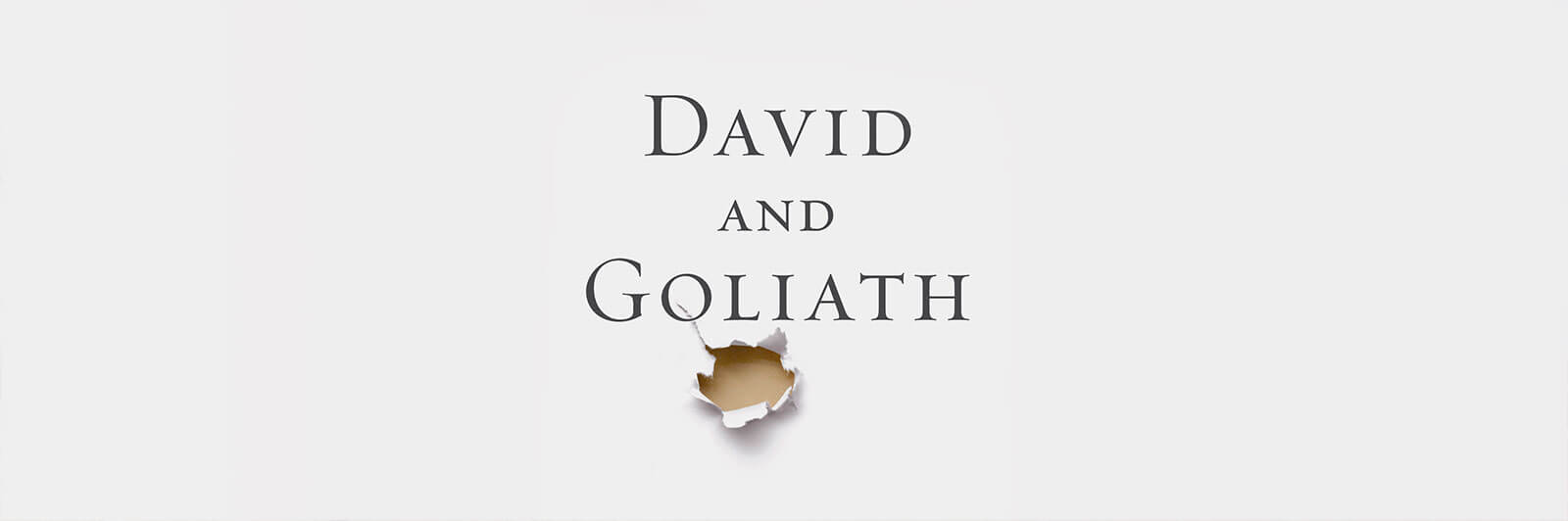 "Hole punched through white paper below ""David and Goliath"" title"