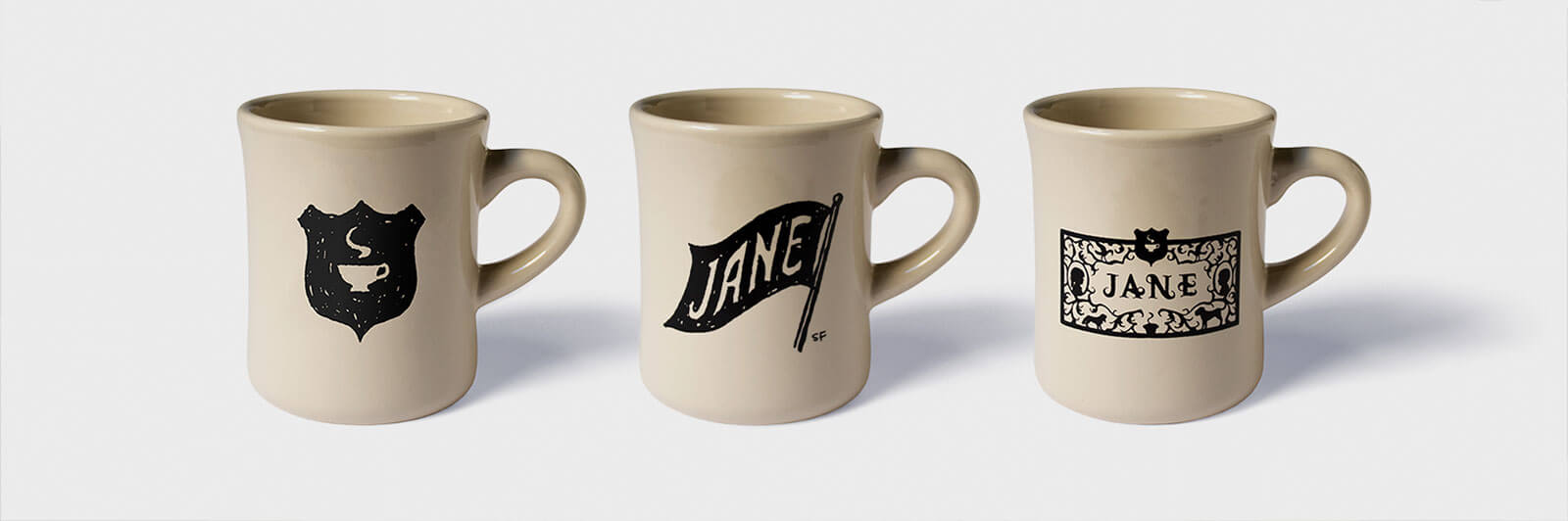 3 light tan mugs with black logos