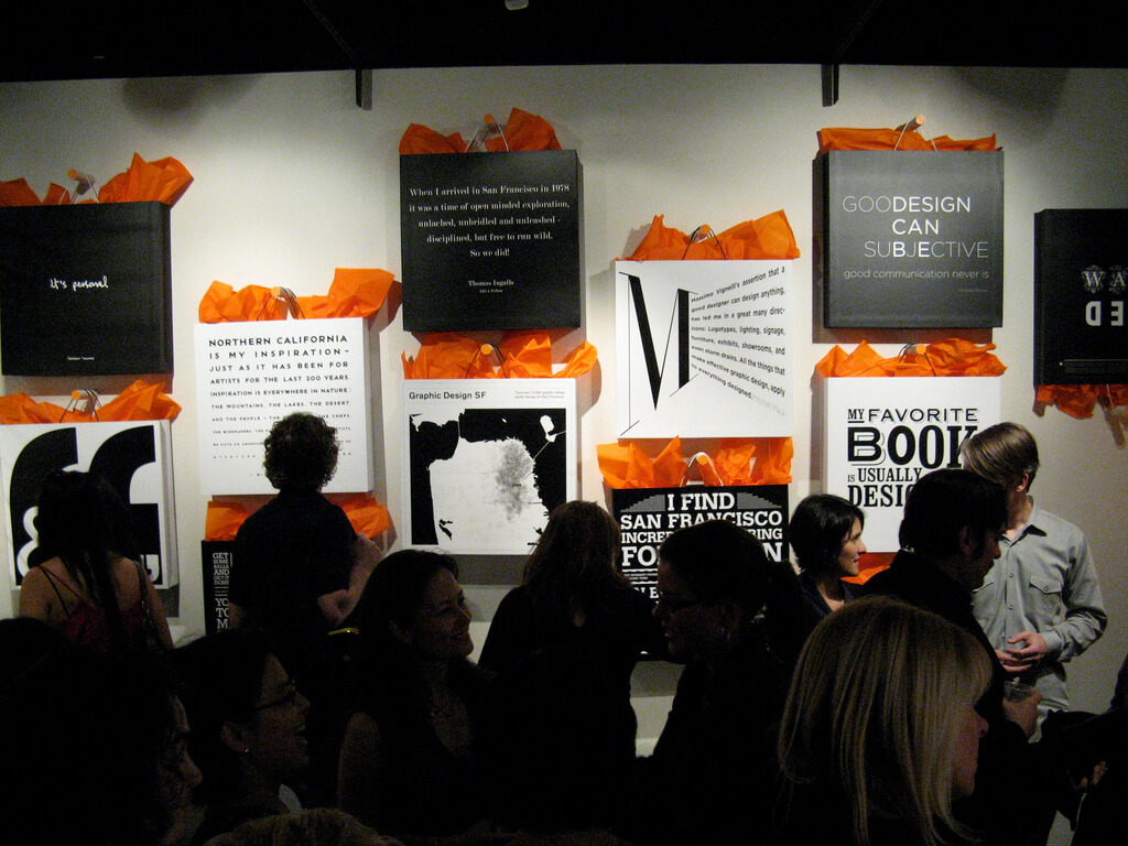 People looking at wall display of black and white shopping bags with orange tissue paper