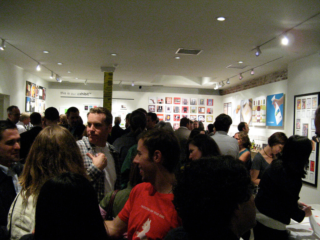 Crowded room at event with artwork on the walls