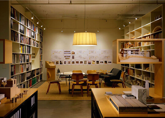 Room with book-filled shelves around table and chairs