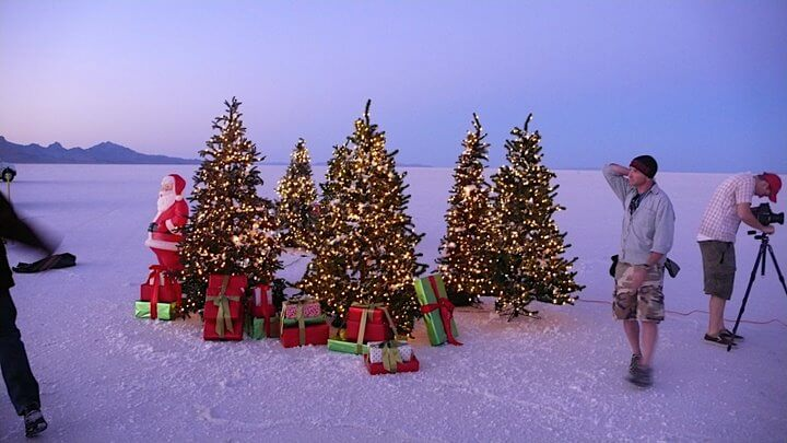 Photography crew with Christmas trees decorated with lights, gifts, and Santa statue