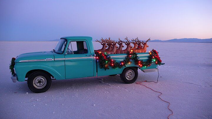 Christmas decorations on turquoise truck filled with fake reindeer
