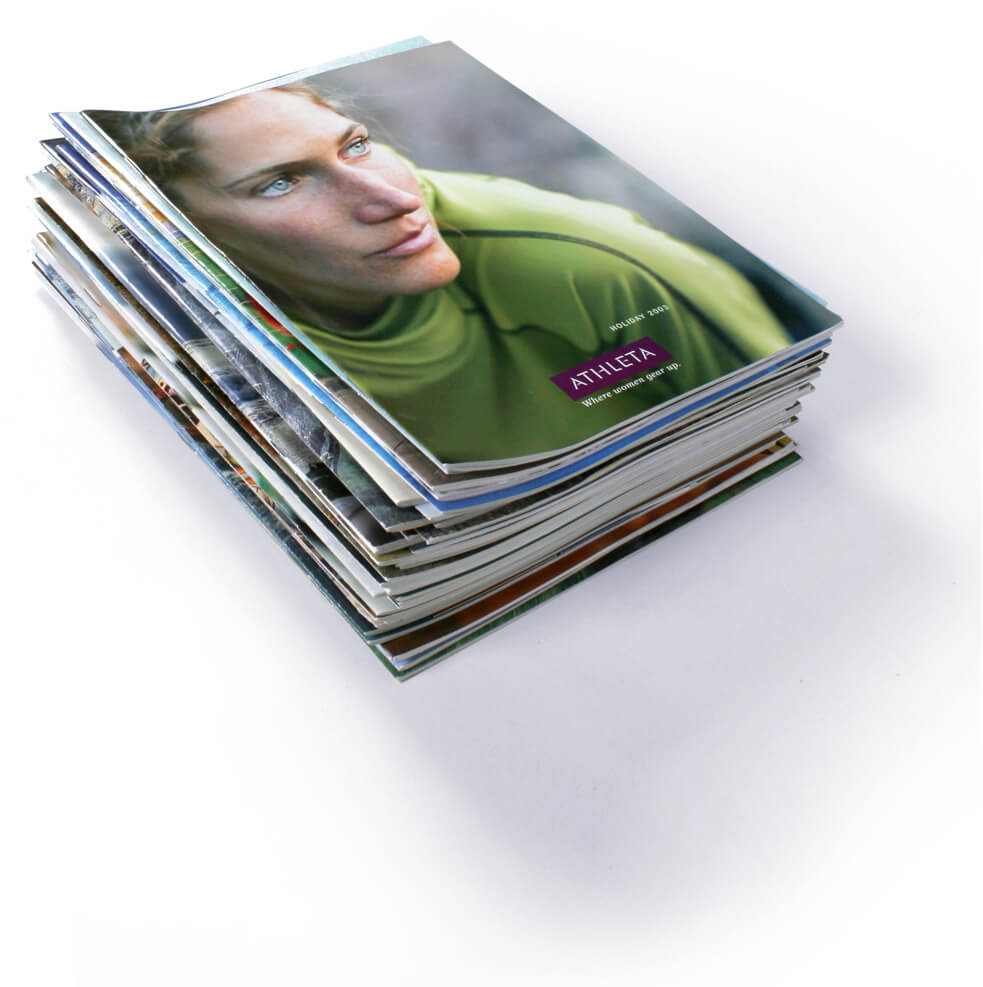 Stack of Athleta catalogs topped with cover of a woman in a green shirt
