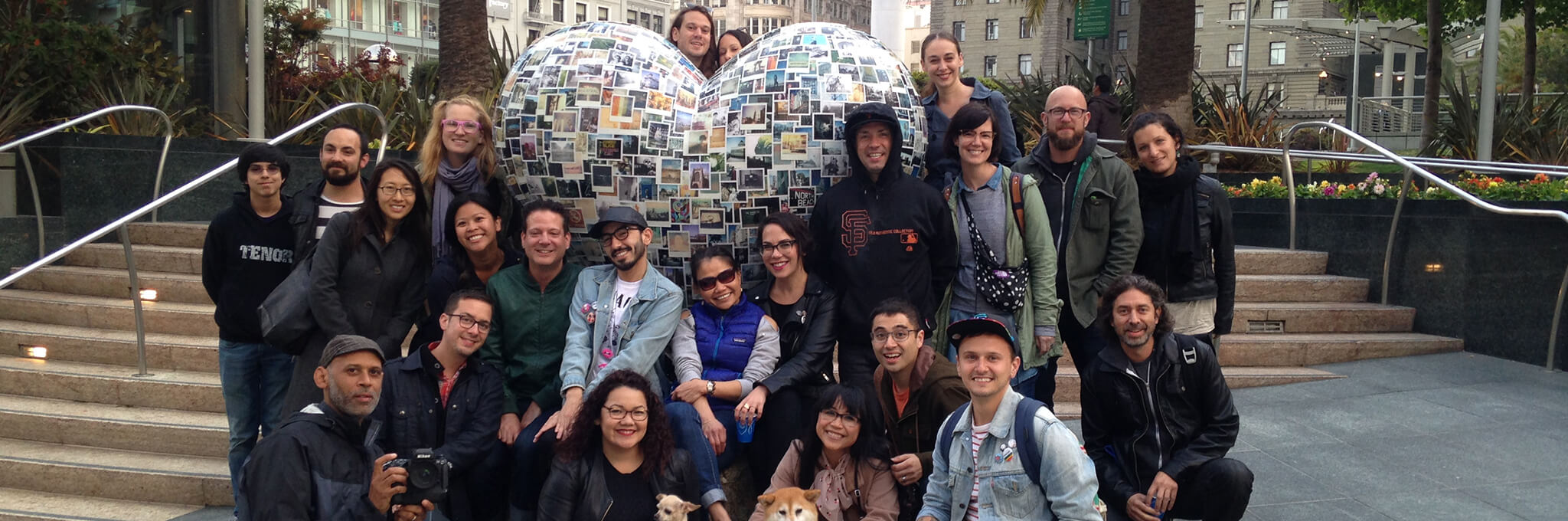 Group of people in front of polaroid-covered heart sculpture
