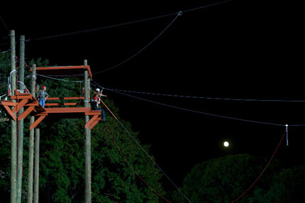 Harnessed person about to jump of orange ledge with small moon in the background