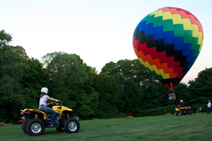 Person on yellow ATV driving towards rainbow-patterned hot air balloon in a field