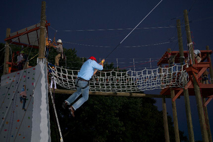Person with blue shirt swinging from rope at night