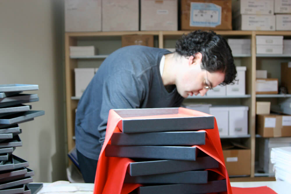 Nate behind stack of gray boxes with red tissue paper