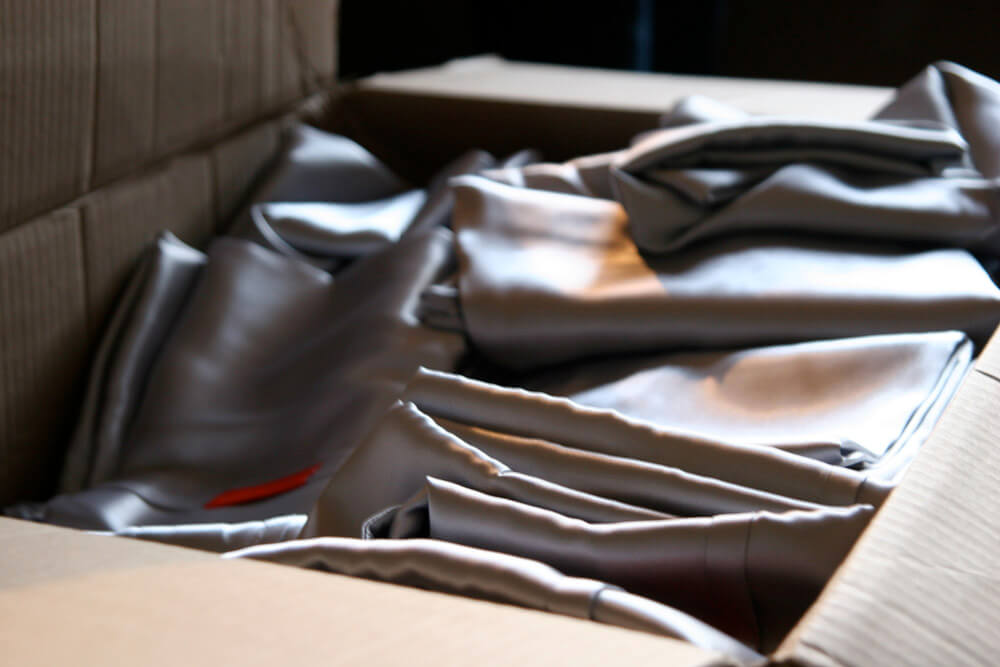 Folded silver pillow cases stacked in cardboard box