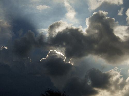 Light peering out from behind clouds in partially dark sky