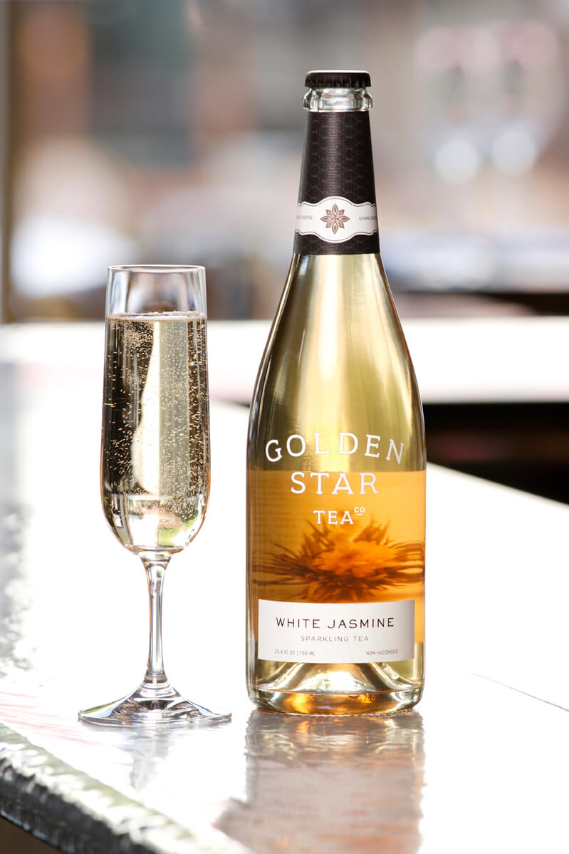 Filled champagne glass next to bottle of Golden Star Tea White Jasmine