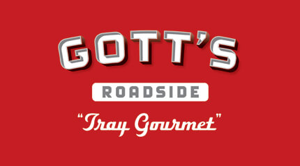 Silver and white Gott's Roadside logo with Tray Gourmet tagline on red background