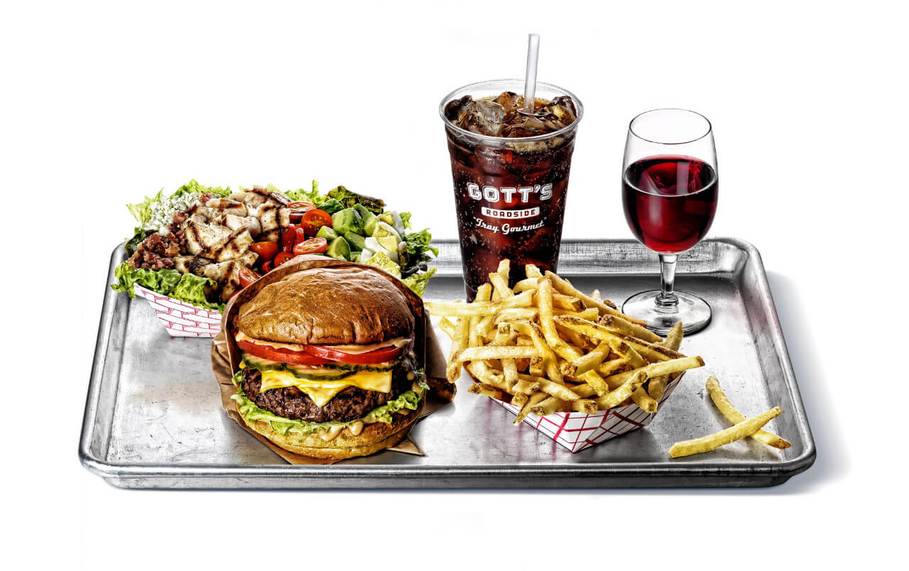 Silver tray with chicken salad, cheeseburger, soda, wine, and fries