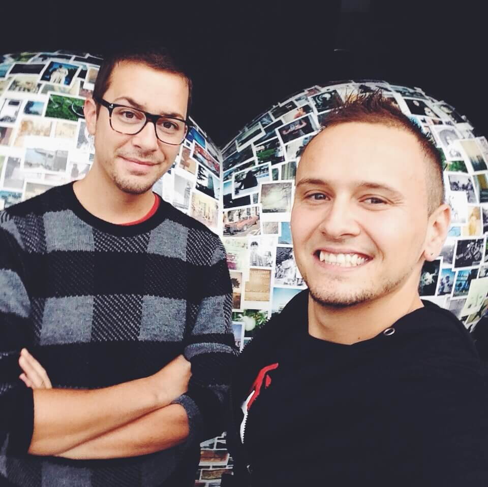 Bruce and Billy selfie in front of polaroid-covered heart sculpture