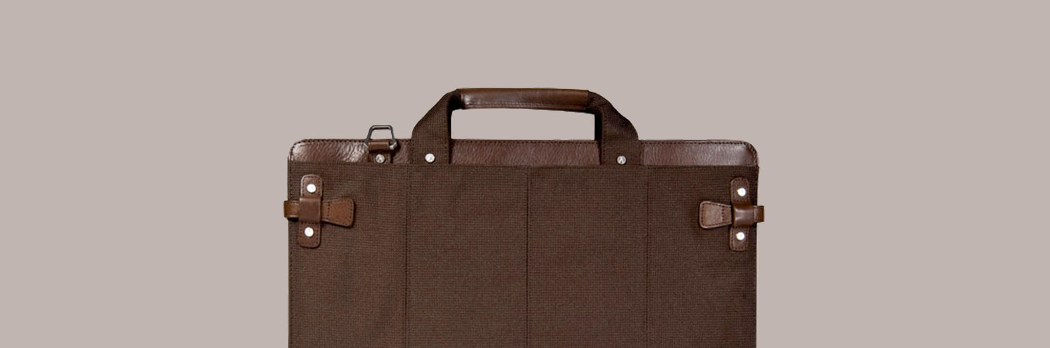 Top portion of brown briefcase on tan-gray background