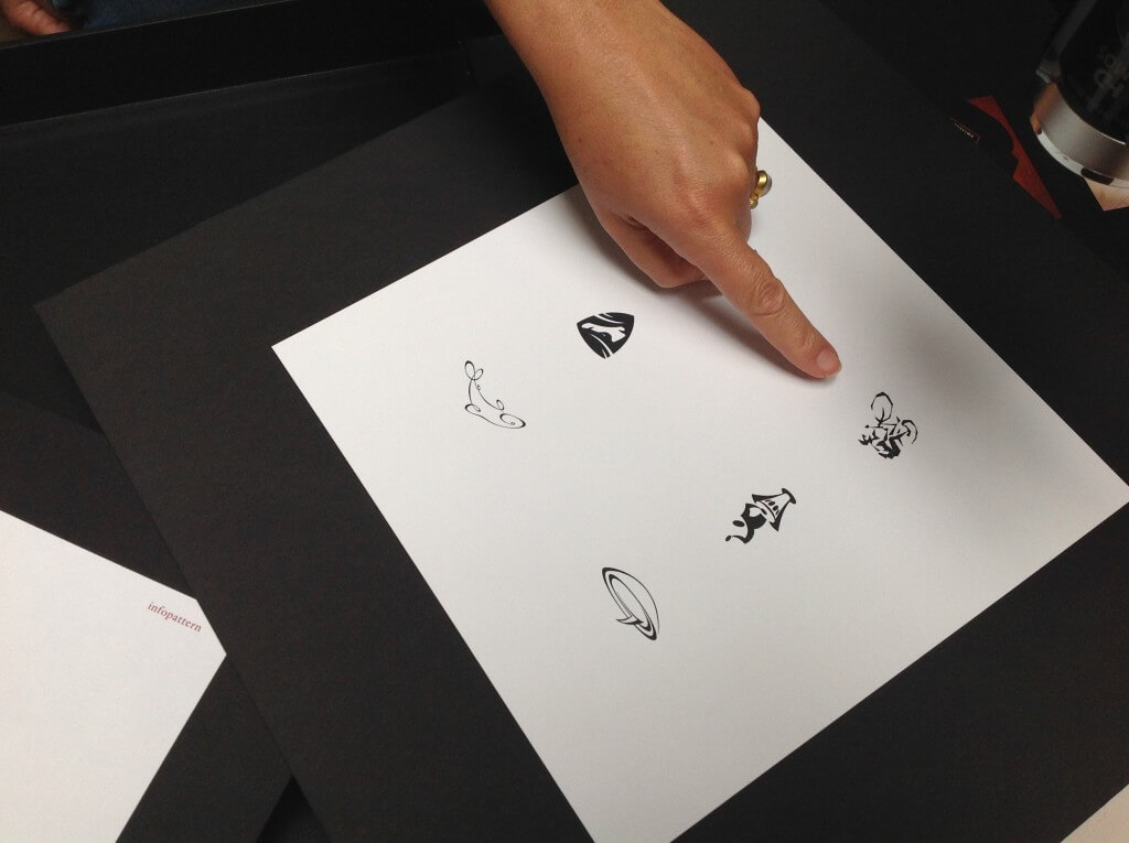 Someone pointing at cyclist logo on a sheet of logo options