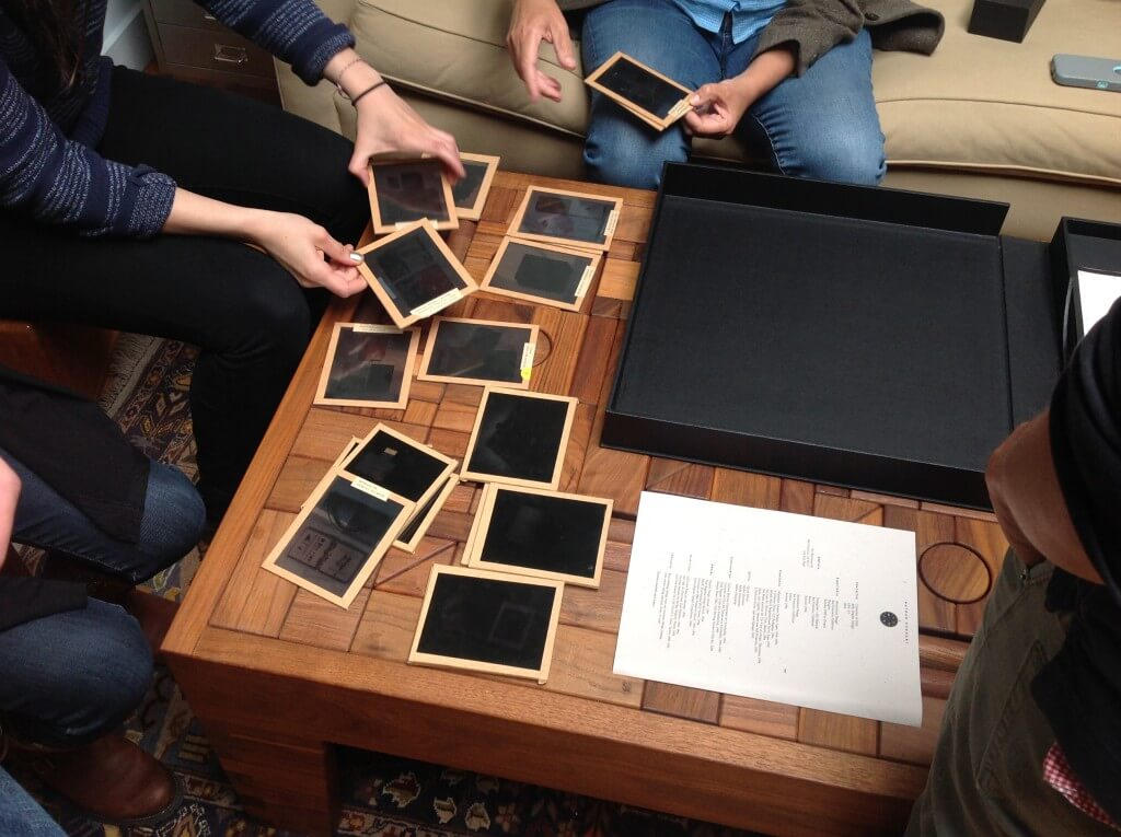 People looking at dark transparency slides at wooden table