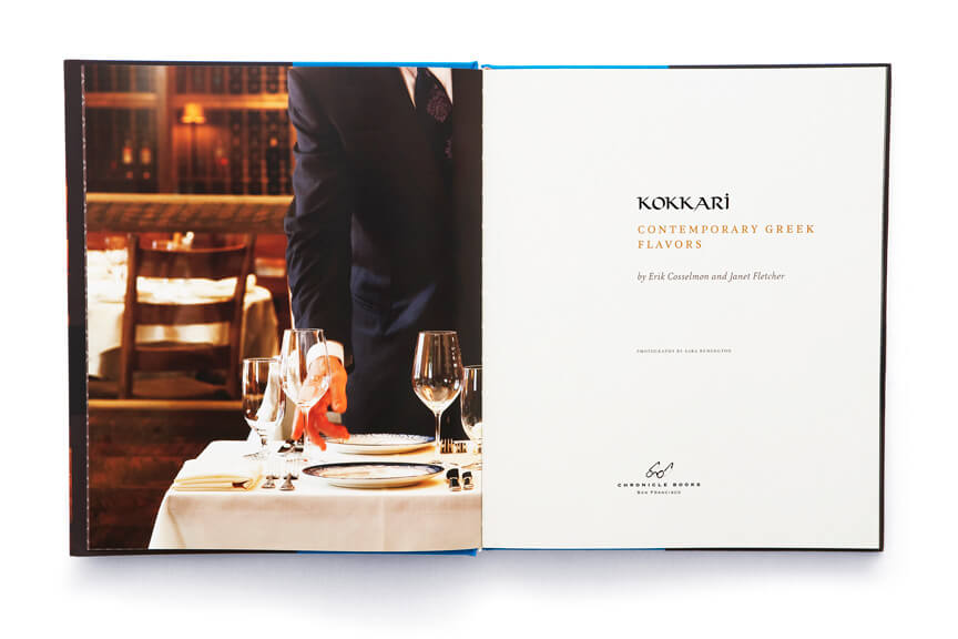 Open book showing suited man setting up glasses at dinner table adjacent to Kokkari title page