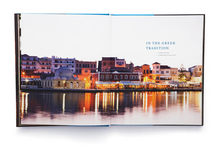 Open book showing seaside town of houses and buildings with reflections in the water