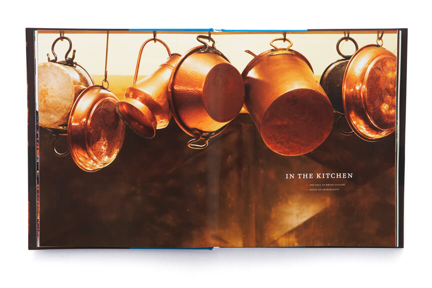 Open book showing copper pots and pans hanging from hooks