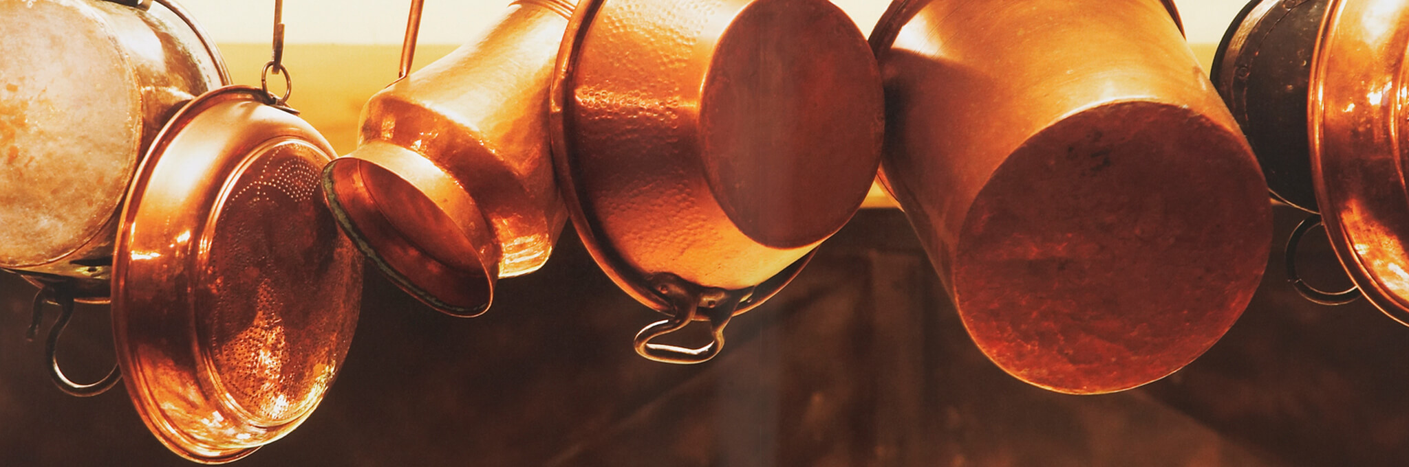 Copper pots and pans hanging from hooks