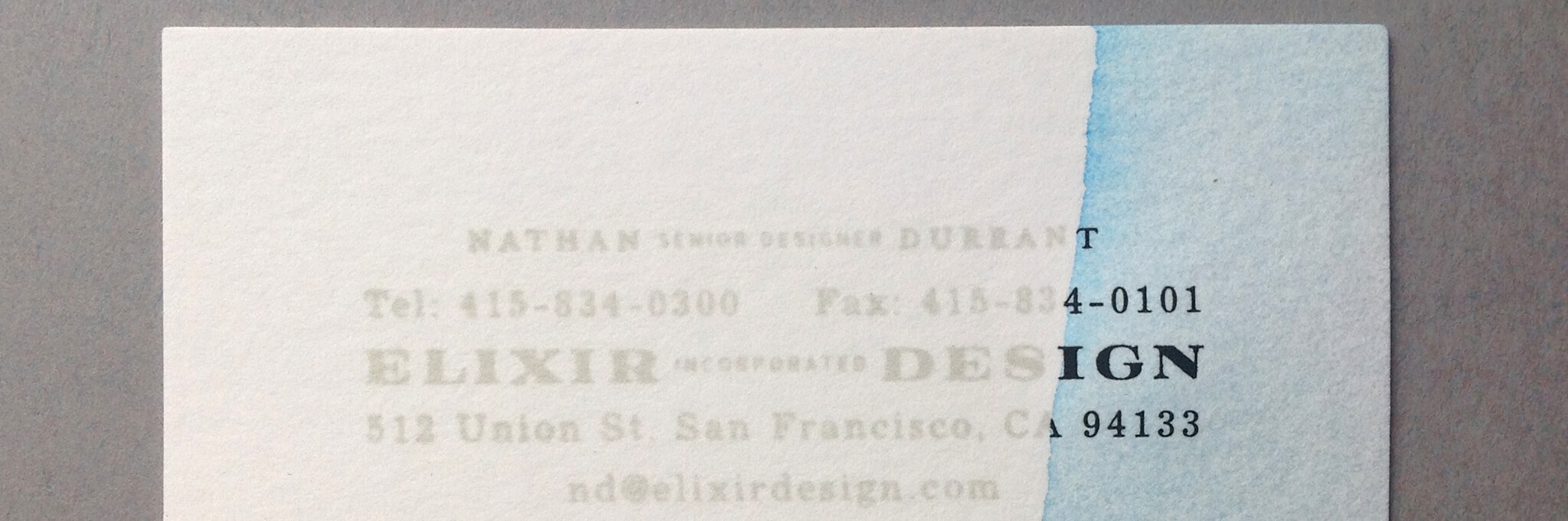 White business card partially dipped in light blue ink on right side