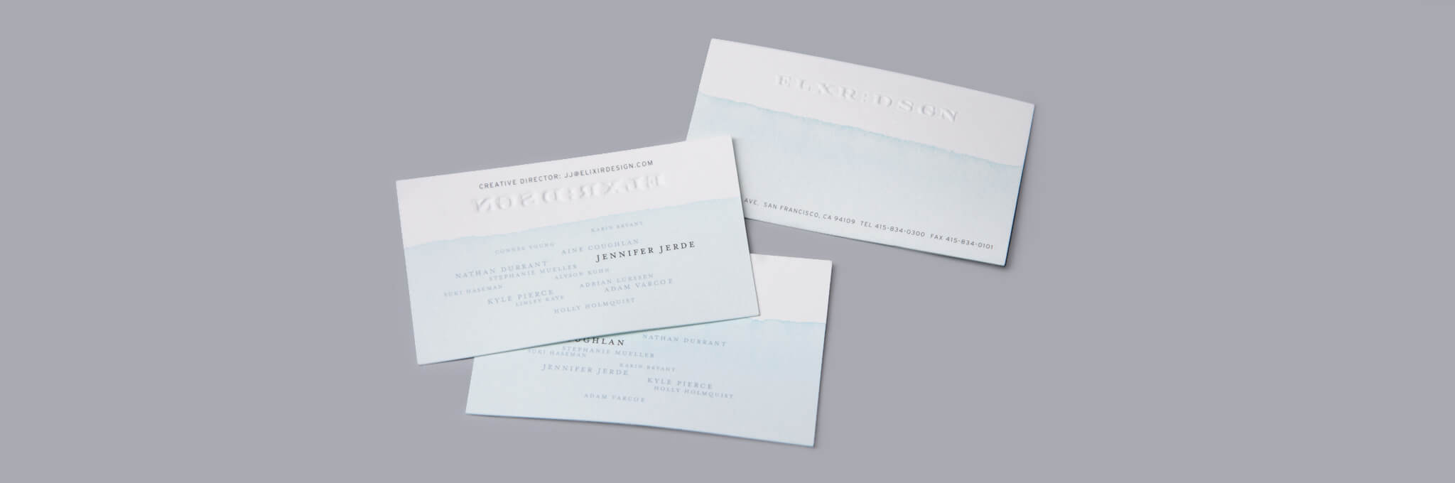 3 white business cards partially dipped in light blue ink on gray background