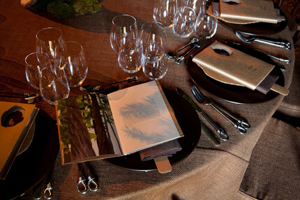Table settings with glasses and program books on plates