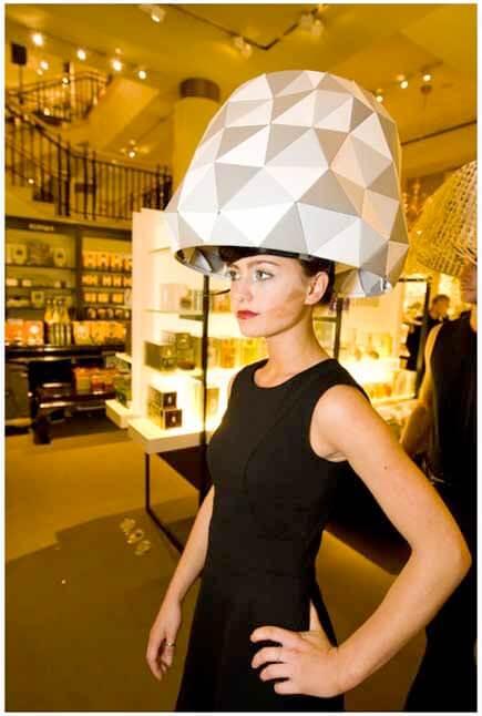 Woman wearing white geometric lampshade headdress
