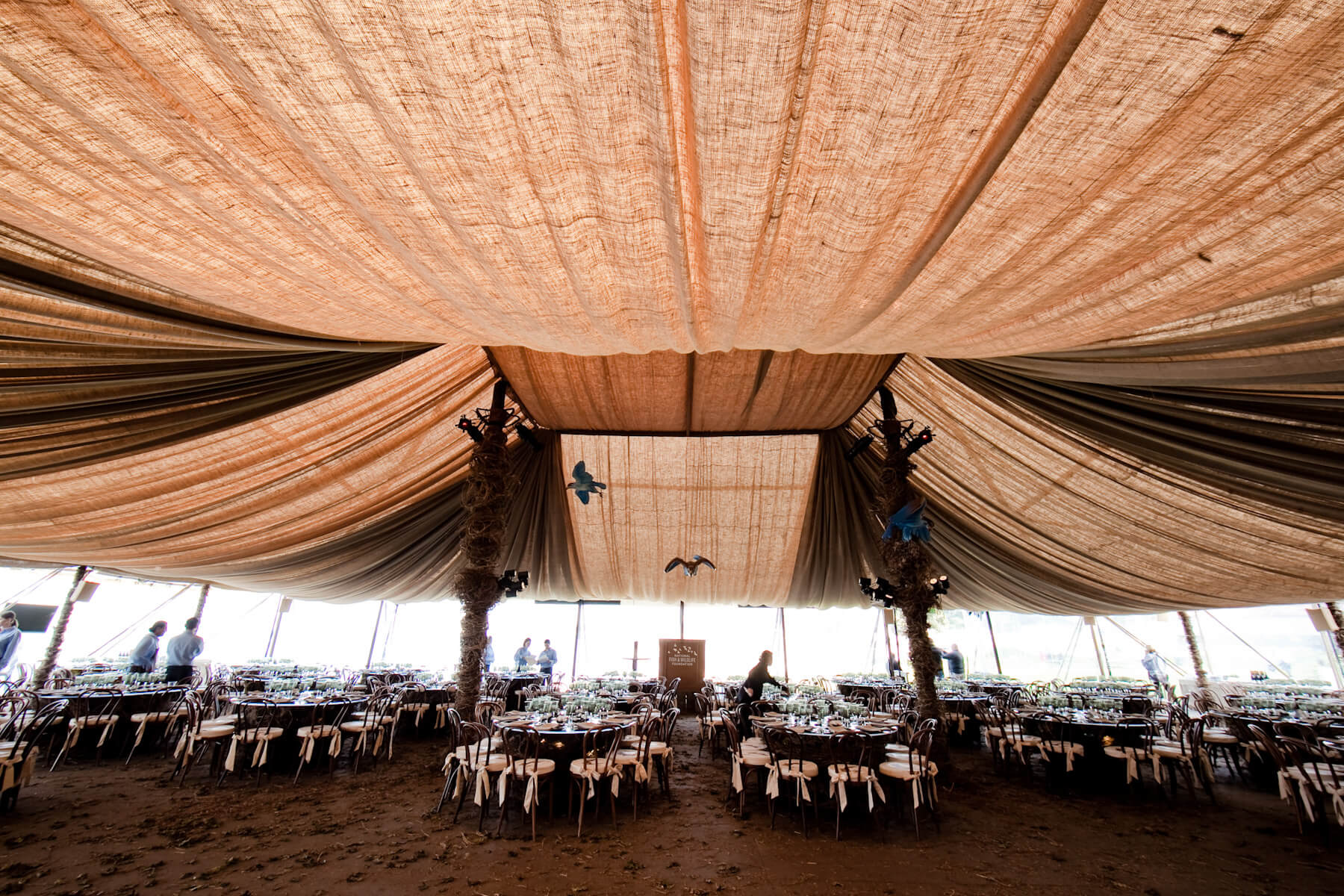 Peach and tan cloth draped ceiling above dinner tables