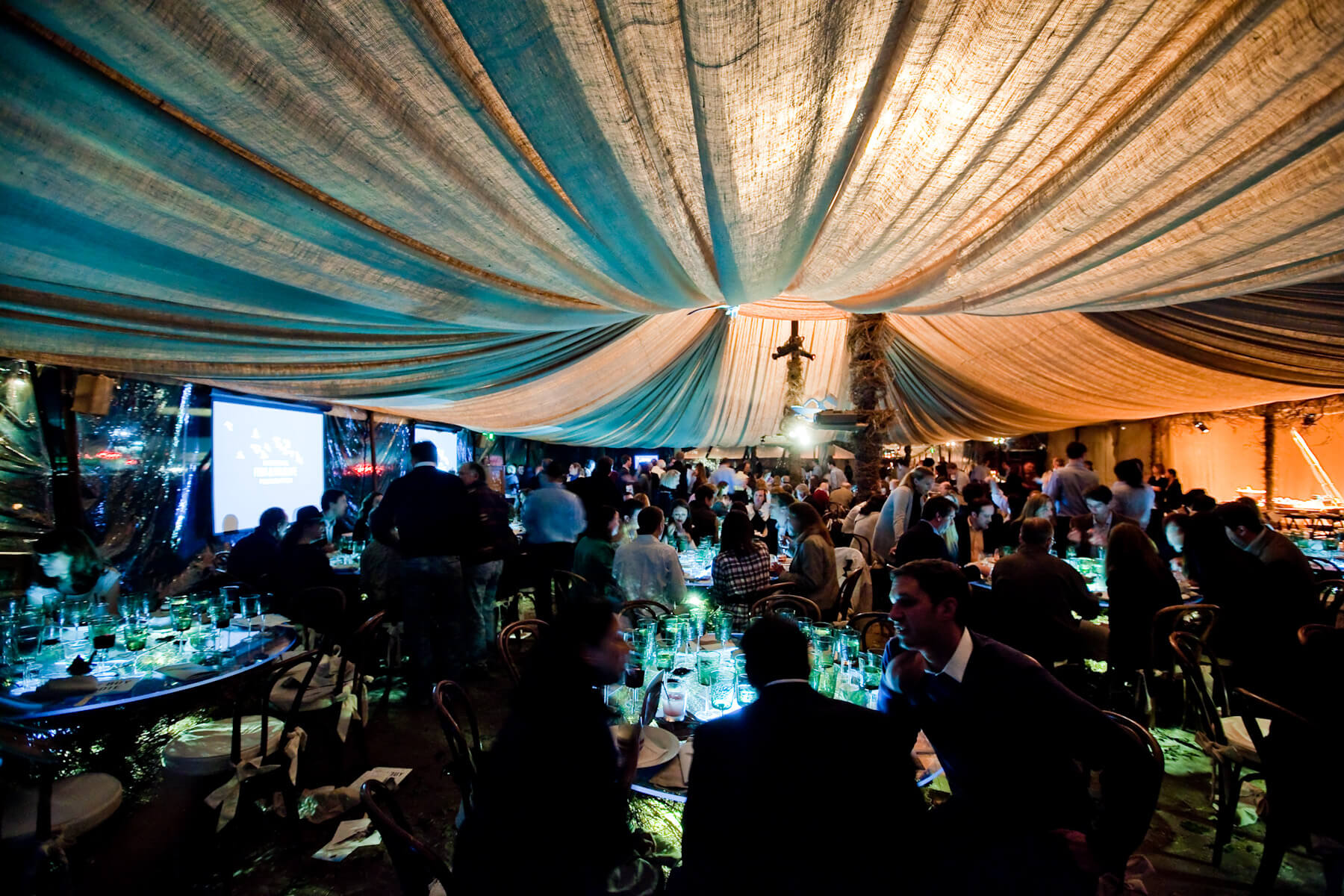 Blue and white draped ceiling above crowds of guests at dinner tables