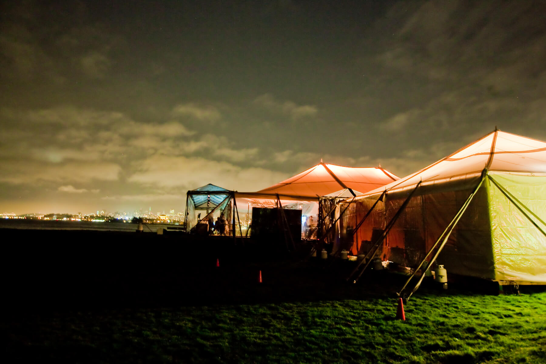 3 blue and orange lit tents in field at night