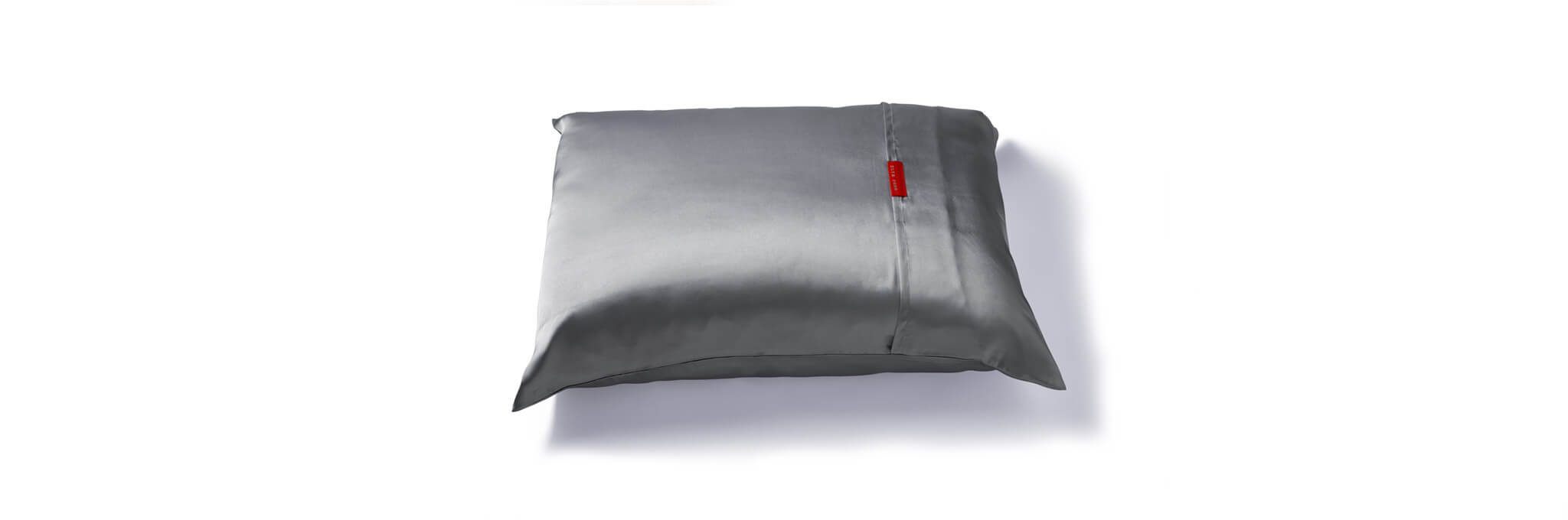 Silver pillow with red tag