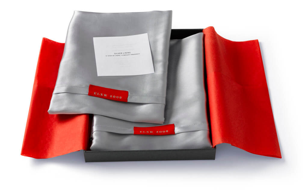 2 folded silver pillow cases in an open dark gray box with red tissue paper