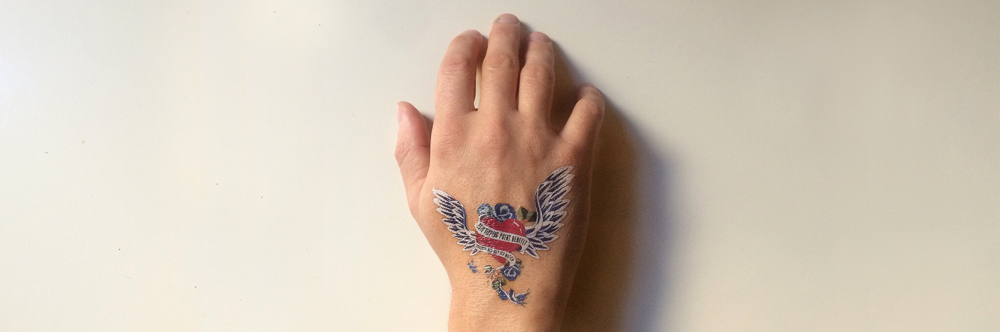 Back of right hand with winged-heart tattoo
