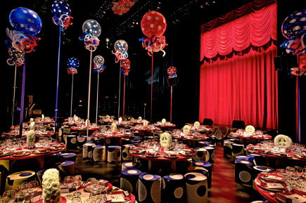 Gala room with red, white, blue table decor, balloons, and red curtain