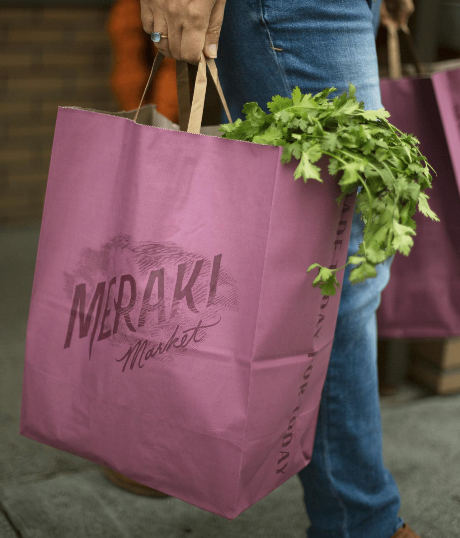 Person carrying pink Meraki cloud logo grocery bag with greens peeking out