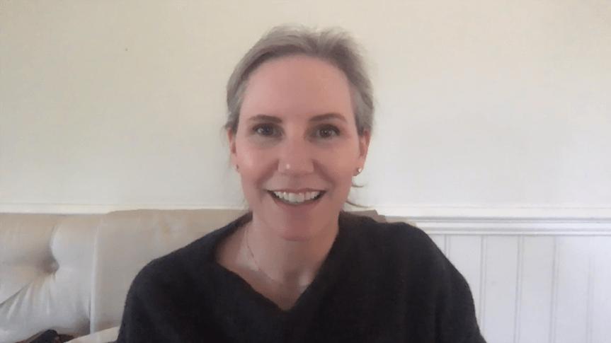 Screen shot of Meagan smiling on white sofa